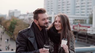 Two happy young people have fun. Handsome young man and beautiful girl laugh joyfully, holding takeaway coffee. Slow mo
