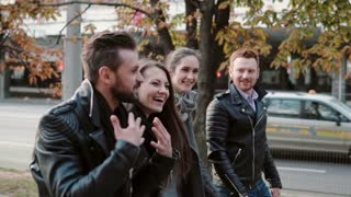 Two pretty young girls and two young men tell jokes and laugh while walking in the street. Steadicam shot, slow mo