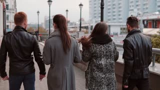 Two trendy girls and two stylish men cheerfully walk in the city and talk. Slow mo, steadicam shot, back view