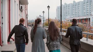 Two trendy girls and two stylish men cheerfully walk in the city, jump and have fun. Slow mo, steadicam shot, back view