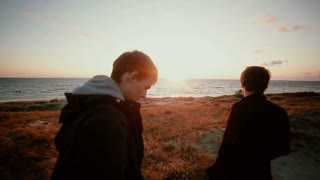 Two young men are standing on sandy dunes at the beach enjoying the view of a gorgeous sunset