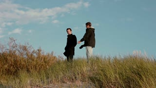Two young men are walking down from a sandy dunes chatting and smiling.