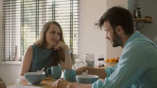 Two young parents having a conversation at the kitchen table while their daughter is colouring. Slow mo, Steadicam shot