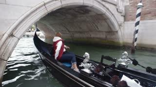VENICE, ITALY - Sep 2013: A gondolier navigates his gondola under a bridge on a canal