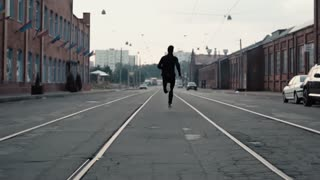 2 in 1. Man running fast in an old city street. Real time. Freedom concept. Camera gets close behind young sportsman.