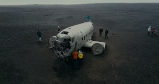 25 MAY 2017, ICELAND. Aerial view of wrecked plane DC-3 in black sand in Iceland. Copter flying over crowd of tourists.