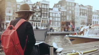 4K 30s happy businesswoman working with laptop. Amsterdam. Lady with red backpack sits on beautiful river embankment.