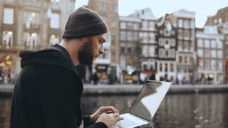 4K Adult 30s businessman uses laptop outdoors. Concentrated man working online. Mobile workplace. Amsterdam old town.