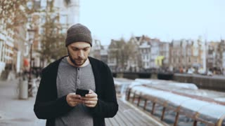 4K Casual concentrated man using smartphone. Handsome bearded creative European male in hat texting in the street.