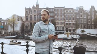 4K Casual man looking around with smartphone. Casual handsome confused bearded man with bicycle near a river embankment.