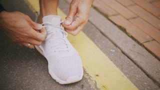 4K Close-up tying shoelaces on a white sneaker. Athlete with a ring lacing white sport shoes on a city asphalt track.