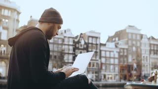 4K Creative man sitting with laptop in the street. Working mobile office. Amsterdam old town. Atmospheric cityscape.