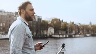 4K European businessman texting on a river bridge. Adult bearded male with bike in blue shirt working in mobile office.