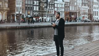 4K European tourist male taking photos outside. Handsome bearded creative male enjoying new town scenery. Wanderlust.