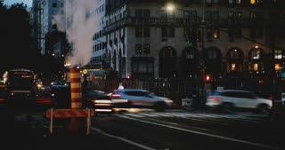 4K Evening to nighttime New York street timelapse. Steam vapor pipe. Busy crowded intersection. Vehicles and people.