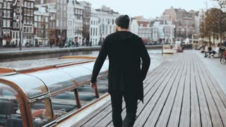 4K Excited casual male traveller on new journey. Looking around. Wanderlust lifestyle. Emotions and feelings. Back view.