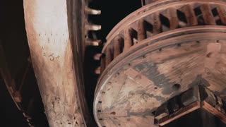 4K Huge wooden cogwheels spin together close-up. Traditional windmill mechanism insides. Ancient clocks rotating fast.