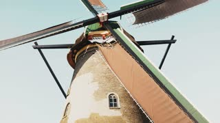 4K Low angle view of traditional old windmill. Netherlands. Dutch historical heritage. Rustic farm mill spinning slowly.