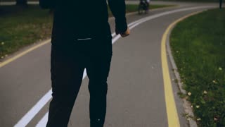4K Man in black sportswear runs in a green park. Back view. Sportsman exercising on a quiet city alley. Lifestyle shot.
