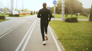 4K Man running along a city park road. Back view. Fitness runner in black sportswear, white sneakers. Healthy lifestyle.