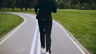 4K Man runs along an autumn park road. Back view. Sportsman jogging on a peaceful quiet park road alley. Lifestyle shot.