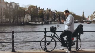 4K Man with bicycle on river bridge with a phone. Casual handsome European bearded male types a message and walks away.