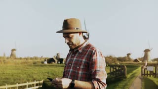 4K Portrait of successful European farmer male. Man in shirt and hat, with smartphone and smart watch walks to a mill.