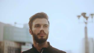 4K Portrait of thoughtful man looking forward. Bearded Caucasian handsome male in sunlight glare modern city background.
