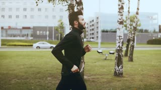4K Profile of sportsman run fast near city street. Real time. Side view. Handsome bearded European man jogging exercise.