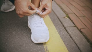 4K Sportsman tying shoelaces, preparing to start. Panning up and left. Professional athlete before running a tough race.