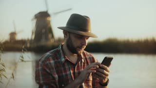4K Successful Caucasian man sits near sunset lake. Farming businessman in a hat using smartphone app. Mobile office.