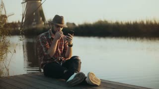 4K Successful European farmer sits on a lake pier. Man in checked shirt and hat using smartphone. Mobile shopping app.