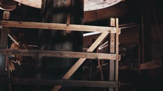 4K Traditional mill mechanism working close-up. Huge old wooden Dutch windmill core spinning inside. Ancient technology.