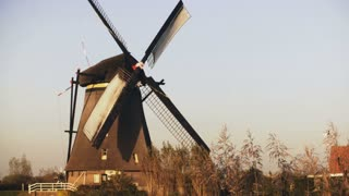 4K Traditional old Dutch rustic windmill working. Netherlands. European historical landmark. Farm mill spinning slowly.