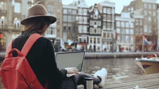 4K Young beauty blogger working with laptop. Amsterdam. Freedom. Girl with red backpack in stylish hat on river quay.