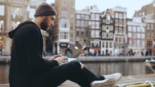 4K Young Caucasian man works with laptop outside. Creative worker looking for inspiration in beautiful old town scenery.