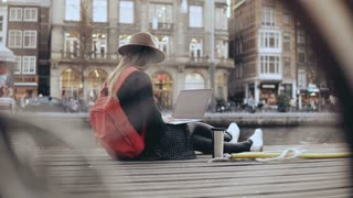 4K Young fashion blogger sitting with laptop. Creative worker outdoors. Freedom. Lifestyle shot through a bicycle wheel.