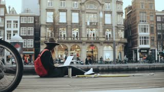 4K Young traveler girl sits outside with laptop. Lively Amsterdam old town street, pigeon, boat and bikes passing by.