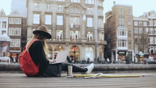 4K Young traveler woman in the street with laptop. European lady sitting in the street with red backpack and thermomug.