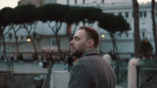 A handsome man considers sights in centre of Rome in Italy in the evening, look around and enjoys the trip. Slow motion.