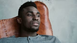 A young African male sitting in the chair, looking into the distance and thinking about something. Man looks thoughtful.