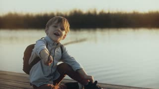 Adorable boy sits with a stick on lake pier. Portrait of little Caucasian child talking, looking at camera joyfully. 4K.
