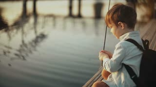 Adorable Caucasian boy plays with stick near lake. Little cute child with backpack on a pier. Happy childhood. 4K.