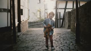 Adorable European boy singing in the street. Male child holds a teddy bear. Talent expression. Old paved town road. 4K.