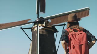 Adult woman walks up to a rustic windmill. Incredible cinematic low angle. Local girl in hat looks at farm mill. 4K
