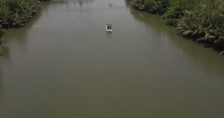 Aerial camera follows small white boat sailing very slow along beautiful calm river in the middle of rainforest jungle.