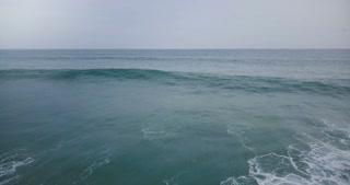 Aerial drone flyover shot of big ocean wave crashing with white foam in breathtaking dark blue open ocean and skyline.