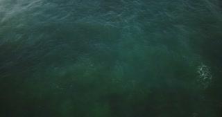 Aerial drone lockdown shot of foaming wave breaking in open ocean. Beautiful vertical view of blue foaming sea water.