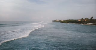 Aerial drone shot of amazing foaming ocean waves reaching and breaking at tropical resort shore with hotels and houses.