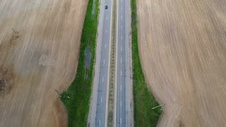 Aerial drone shot of empty motorway. Car driving through the road at the countryside, through the field.